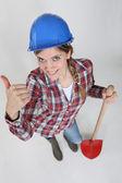 Young female bricklayer holding shovel — Stock Photo