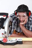 A man staring at a circular saw. — Stock Photo