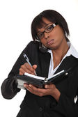 A busy black businesswoman. — Stock Photo