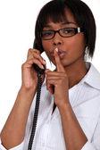 Vrouw praten over de telefoon en haar vinger te houden aan haar lippen — Stockfoto