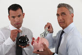 Two businessmen putting money in piggy-banks — Stock Photo