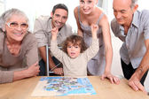 Family gathered around jigsaw puzzle — Stock Photo