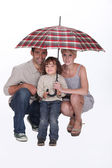 Young family crouching under an umbrella — Stock Photo