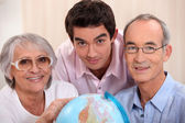 Grown-up family looking at a globe — Stock Photo