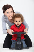 A mother and her son playing with a steering wheel — Stock Photo
