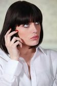 Brunette woman at phone looking surprised — Stock Photo