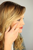 Beautiful blonde in profile applying cream — Stock Photo