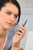 Woman concentrating with a pen in her hand — Stock Photo