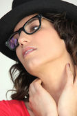 Studio portrait of a woman in thick rimmed glasses and a black hat — Stock Photo