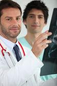 Two medics examining an X ray — Stock Photo