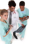 A team of medical professionals discussing the results of a patient's — Stock Photo