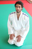 Adult male kneeling on mat in martial arts clothing — Stock Photo