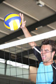 A volleyball player hitting the ball over the net. — Stock Photo