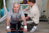 Mature man training with fitness coach — Stock Photo