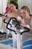 Young women using exercise equipment — Stock Photo