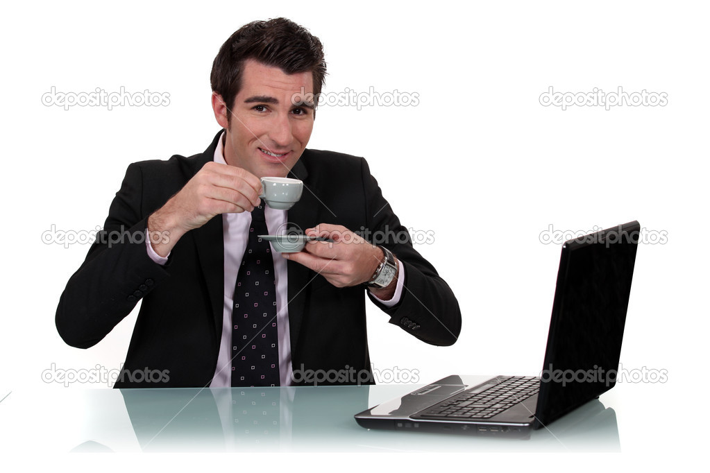 Handsome businessman with laptop having cup of coffee — Stock Photo #8112358