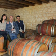 Three drinking wine in a cellar — Stockfoto