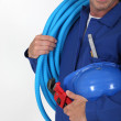 Man holding blue tube, wrench and hardhat — Stock Photo