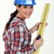 Construction worker measuring a piece of wood - Foto Stock