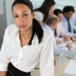 Businesswoman in front of a busy team — Stockfoto