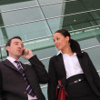 Pair of execs using a cellphone outside an office building — Stock Photo #8128772