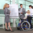 Businesswoman in wheelchair with colleagues — Stock Photo