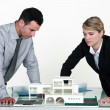 Two architects examining scale model of housing - Foto de Stock