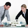 Two architects examining scale model of housing - Stock Photo