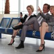 Stock Photo: Businessmen and women in departure lounge.