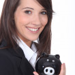 Young woman smiling with a piggy bank - Stock Photo