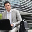 Businessman sat outside with laptop computer — Stock fotografie