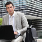 empresário sentou-se fora com o computador portátil — Foto Stock