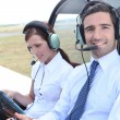Smiling man sitting in the cockpit of a light aircraft as his partner consu — Stock Photo #8129124