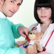 Medical team operating on a teddy bear - Stock Photo