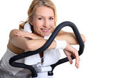 Portrait of a woman on exercise bike — Stock Photo