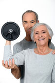 Older couple working out with weights — Stock Photo