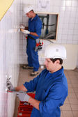 Electricians working in a tiled room — Stock Photo