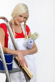Cheeky young female decorator with her hair in plaits — Stockfoto