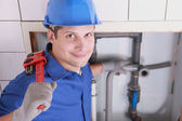 Handsome young plumber with a wrench — Stock Photo