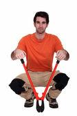 Mann kniend mit bolzenschneider — Stockfoto