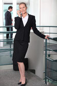 Woman in a skirt suit on cellphone — Stock Photo