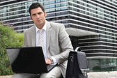 Businessman sat outside with laptop computer — Stock Photo