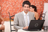 Young man using laptop in a restaurant — Stock Photo