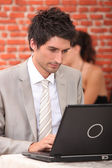 Man working at a laptop in a restaurant — Stock Photo