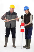 Senior craftsman and young craftswoman nailing a traffic sign — Stock Photo