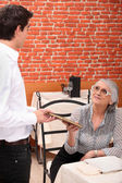 Mature lady being served by waiter at restaurant — Stock Photo