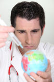 Doctor using syringe on a globe — Stock Photo