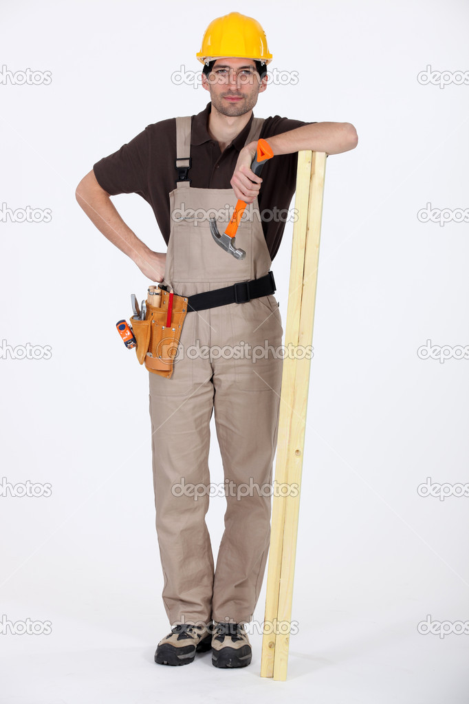 Man stood with plank of wood and hammer — Stock Photo #8128489
