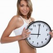 Young sporty woman showing a clock — Stock Photo #8163934