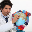 Doctor listening to globe — Stock Photo